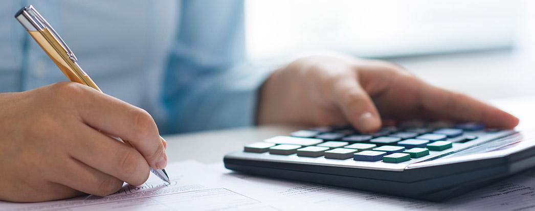 Como contabilizar a venda do ativo imobilizado - pessoa fazendo o cálculo com calculadora, caneta e papel